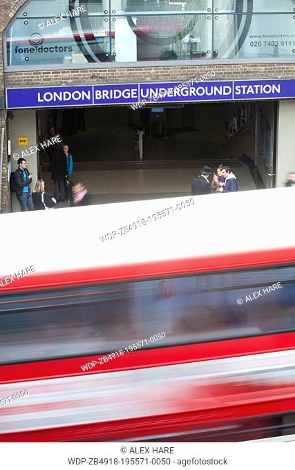 A view of a tradional red London bus as it passes London Bridge underground station