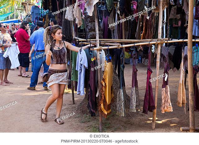 Woman selecting clothes in a market, Anjuna Beach Flea Market, Anjuna Beach, Anjuna, Bardez, North Goa, Goa, India