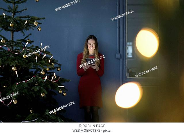 Smiling woman in a loft using tablet at Christmas time