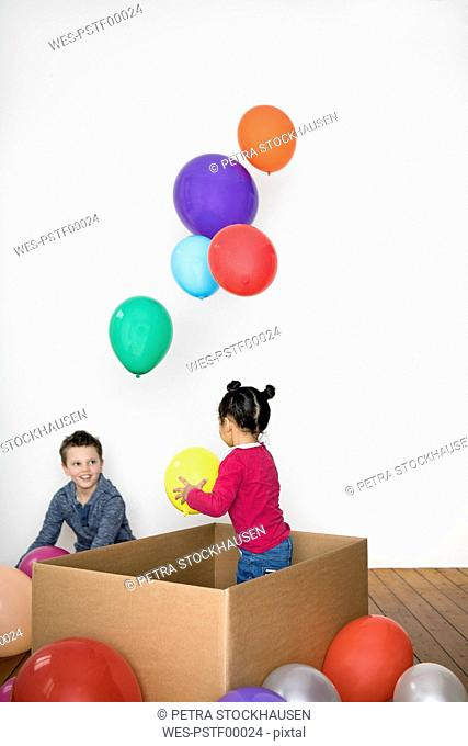 Two kids playing with balloon and cardboard box