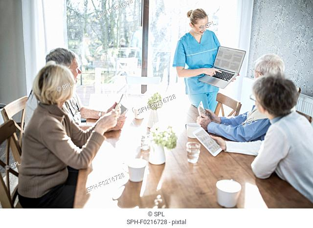 Carer showing seniors laptop