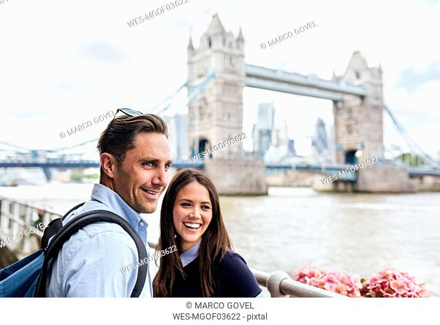UK, London, smiling couple with the Tower Bridge in the background