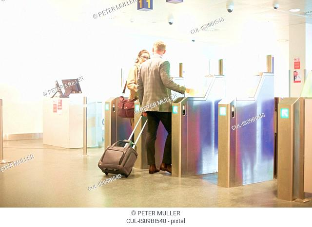 Businessman and woman walking through security gate at airport, low angle view
