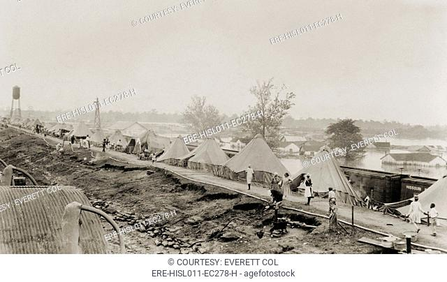 Refugees at a tent city on the levee, with partially submerged houses of Arkansas City in background, during the 1927 Flood