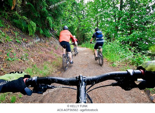 A group of mountain bikers make their way along a sea side trail in Powell river on the upper Sunshine coast of the Vancouver coast and mountain range