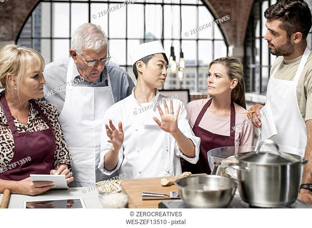 Female chef talking to students in cooking class