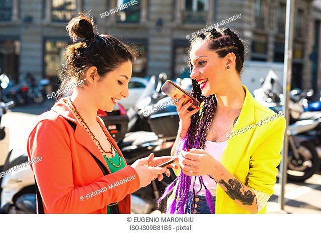 Women in city break using mobile phone, Milan, Italy