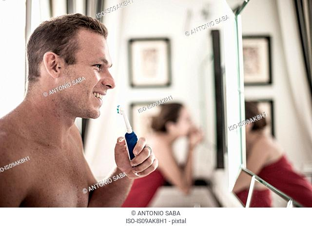 Young couple brushing teeth in his and hers bathroom