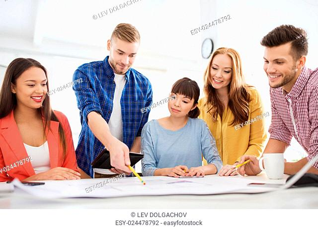 business, startup, education and people concept - creative architect team or students with blueprint working at office