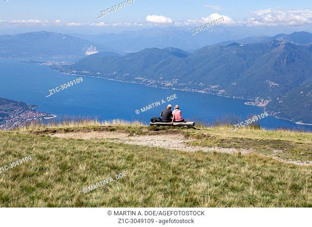 Two tourists contemplating the beautiful view of Lago Maggiore (Lake Maggiore) from the top of Monte Lema (Mount Lema). Veddasca, Italy
