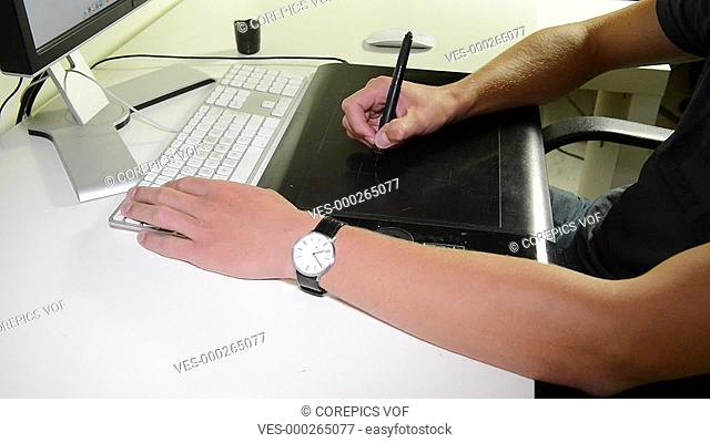 Zooming in on the hands of a graphic designer at work on a tablet and keyboard