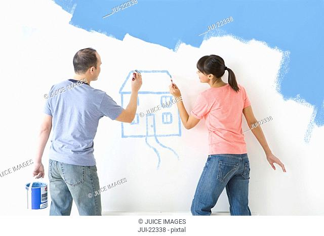 Couple painting house on wall with paintbrushes