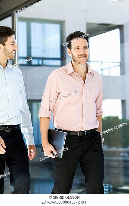 Business associated walking together in office