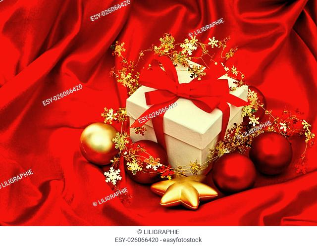Gift box with christmas decoration over silk background. Red gold baubles stars. VIntage style toned picture