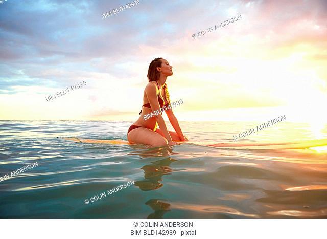 Pacific Islander woman floating on surfboard in ocean
