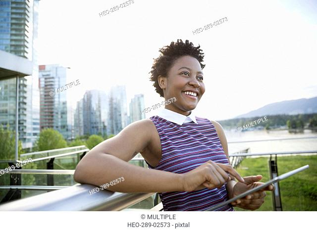 Smiling businesswoman using digital tablet at city waterfront