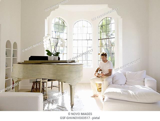 Mid-Adult Man Playing Guitar in Living Room