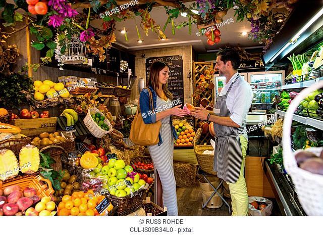 Fruiterer serving customer in shop, Palma de Mallorca, Spain