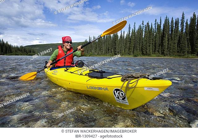 Young woman in kayak, paddling, kayaking, clear, shallow water of upper Liard River, Yukon Territory, Canada