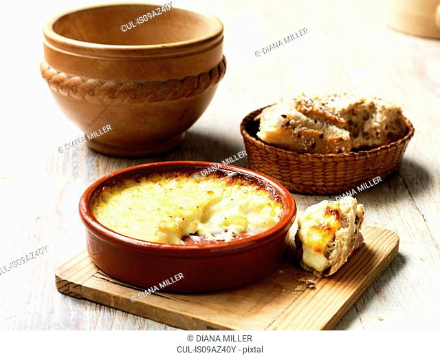 Baked cheese in terracotta dish