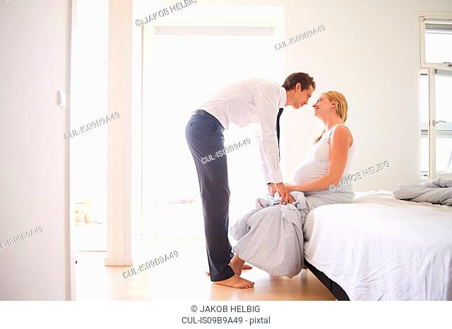 Romantic pregnant couple face to face in bedroom