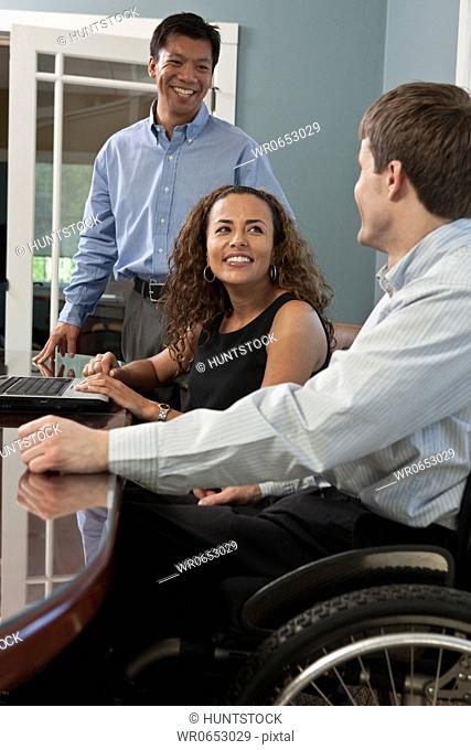 Businessman with spinal cord injury and a visually impaired Hispanic businesswoman in an office