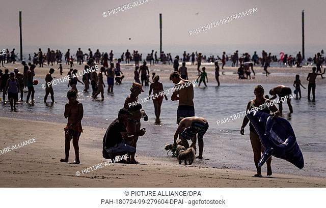 24 July 2018, Germany, Sankt Peter Ording: Beach guests search for refreshment in the water. Photo: Axel Heimken/dpa. - Sankt...