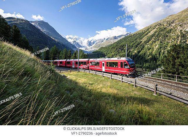 Bernina Red Train and Morteratsch glacier on the background. Engadin, Graubunden, Switzerland