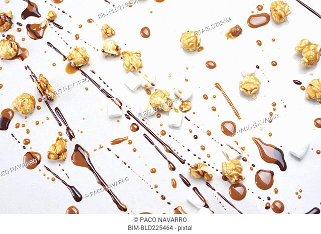 Chocolate, caramel popcorn and marshmallows on white background