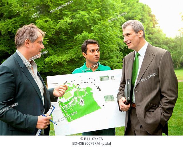 Businessmen examining blueprints in park