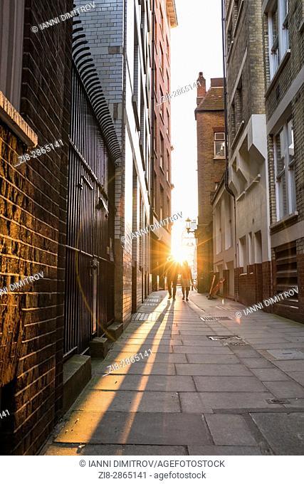 Couple walking the Narrow street towards the setting sun,Lewisham Street,SW1,London,England