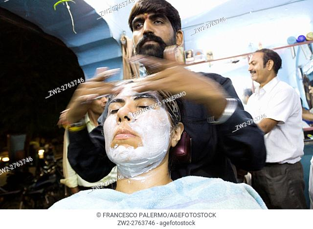 Barber in action with massage and face care. Jaipur, Rajasthan, India