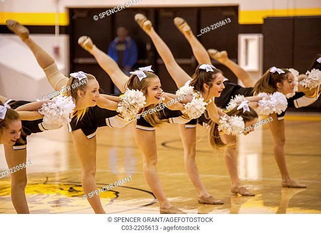 High school cheerleaders perform a deep bow during a basketball game in Mission Viejo, CA