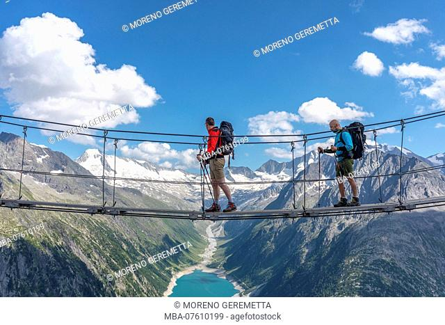 Two hikers on the tibetan bridge near Olperer hut with Schlegeis Stausee on the background, Zillertal Alps, Tyrol, Schwaz district, Austria