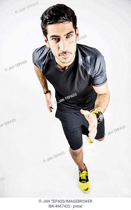 Young man runs in sportswear, studio shot