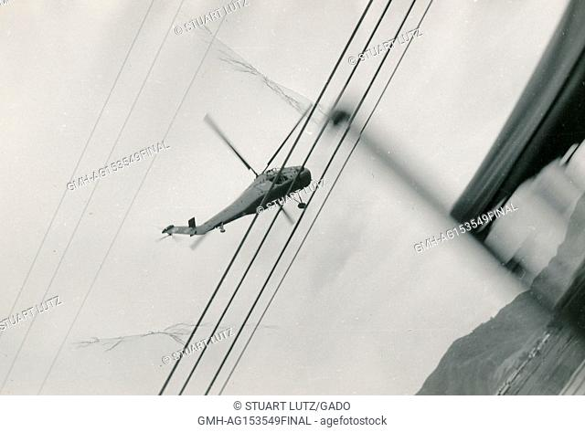 A United States Marine Corps helicopter is seen in mid flight from a moving military vehicle, with power lines in the foreground, during the Vietnam War, 1968