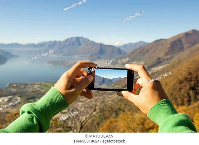 Woman Taking a Photo of the Mountain and Alpine lake Maggiore with Mobile Phone in Ticino, Switzerland