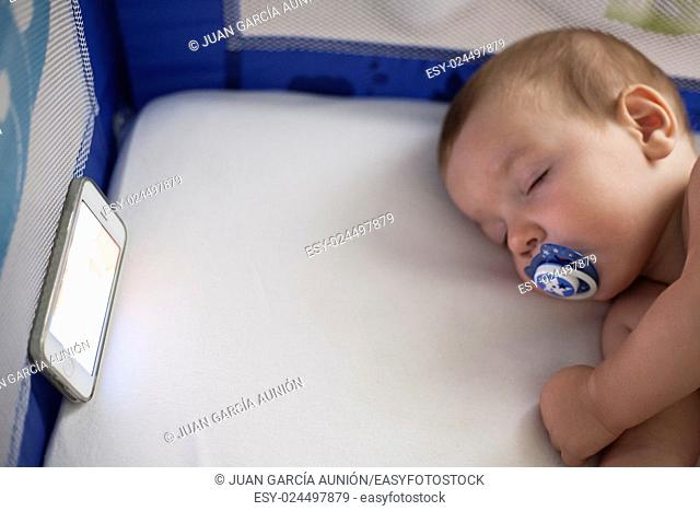 12 month old baby sleeping with a lullaby songs from mobile phone on the crib