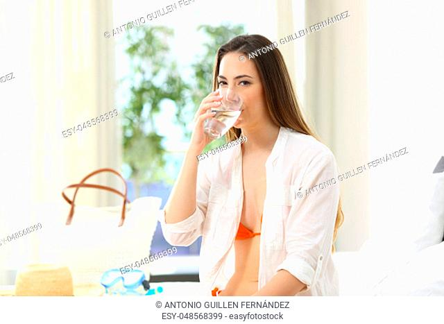 Relaxed tourist drinking potable tap water in an hotel room during a travel on summer vacations