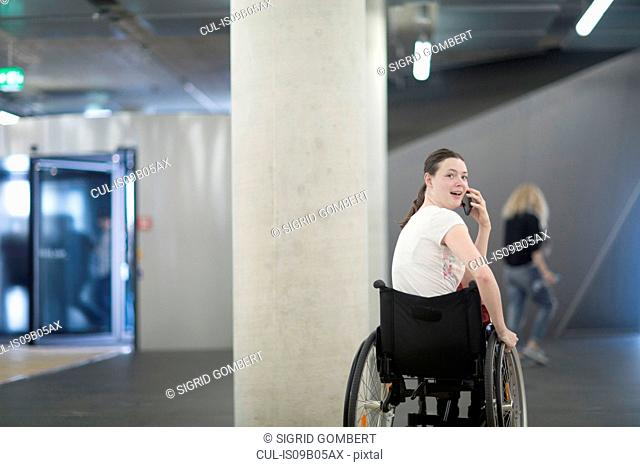 Young woman using wheelchair in underground parking lot talking on smartphone