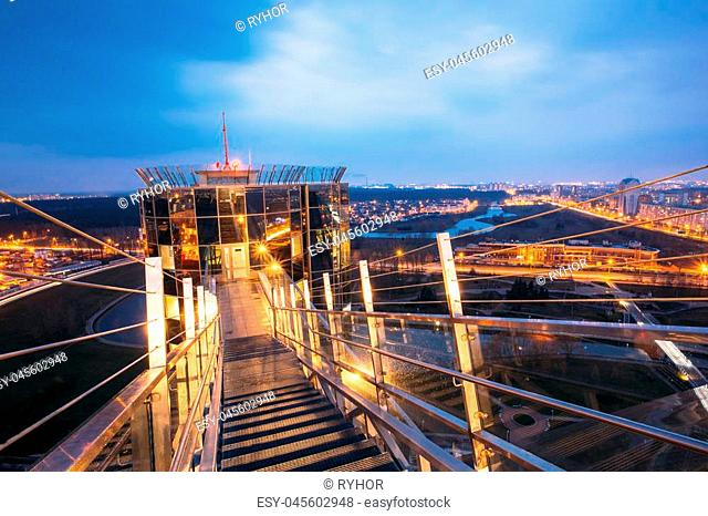 Minsk, Belarus. Observation Deck Viewpoint Lookout On National Library Building. Cityscape In Evening Night Illumination Under Blue Sky Background