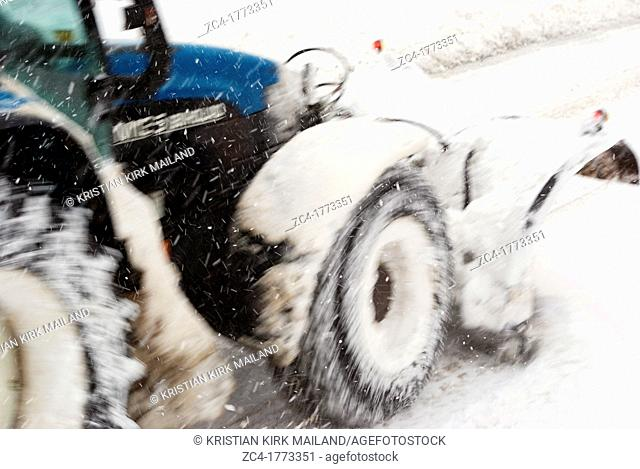 Tractor with snowplow in Scandinavian winterstorm