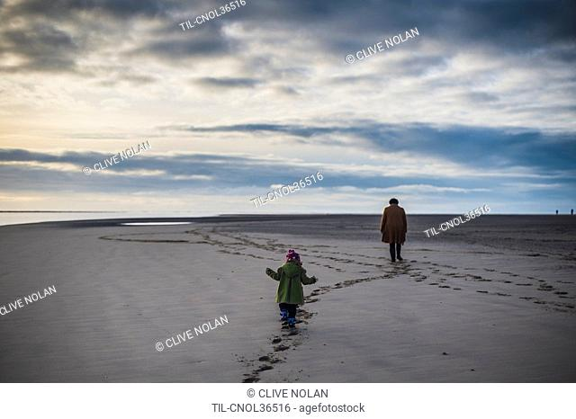 Mother and daughter walking on the beach in winter under grey skies