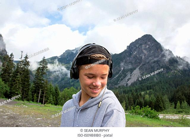 Portrait of teenage boy in rural setting, wearing headphones