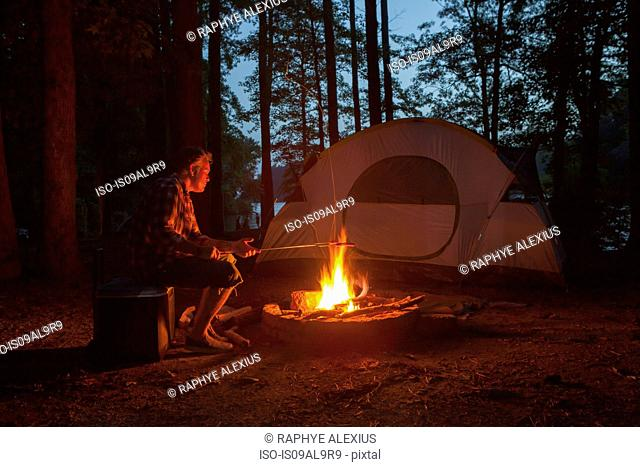 Man cooking on campfire in forest at night, Arkansas, USA