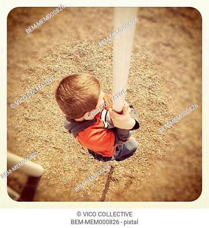 Boy sliding down pole on playground