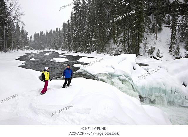 A couple snowshoes towards Mushbowl Falls in Wells Gray Provincial Park, Thompson Okanagan region, British Columbia, Canada