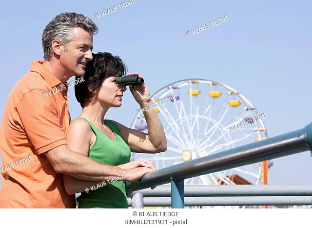 Caucasian couple using binoculars at theme park