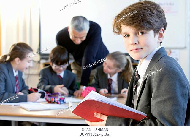 Portrait confident middle school student with notebook in classroom