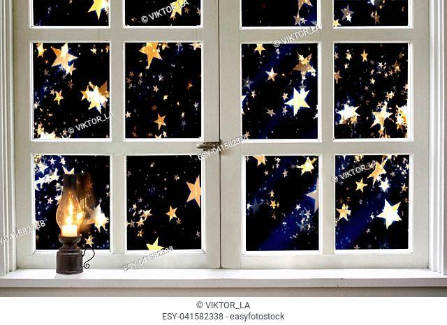 Night window with a lighted kerosene lamp. A fabulous Christmas starfall